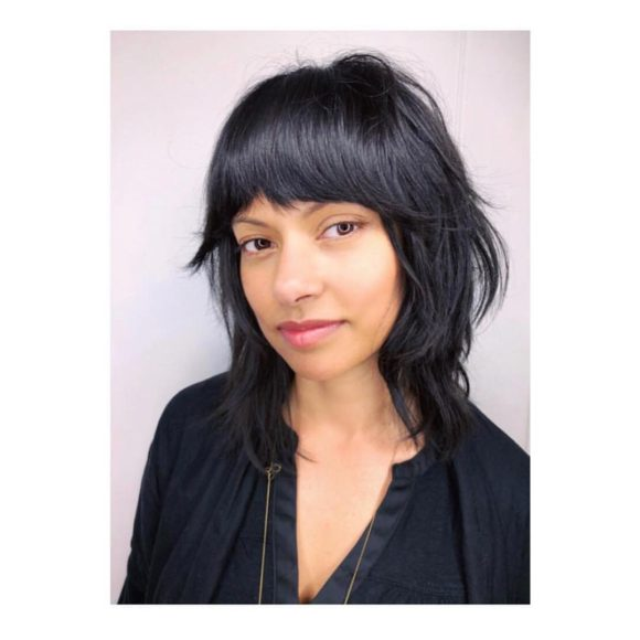 Black Shaggy Razor Cut Bob with Full Fringe Bangs and Undone Texture Medium Length Hairstyle