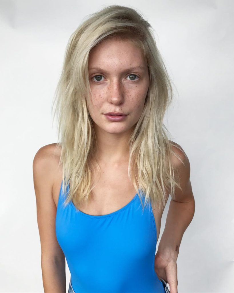 Blonde Layered Cut with Messy Beach Texture and Dramatic Side Part with Long Bangs Medium Length Summer Hairstyle