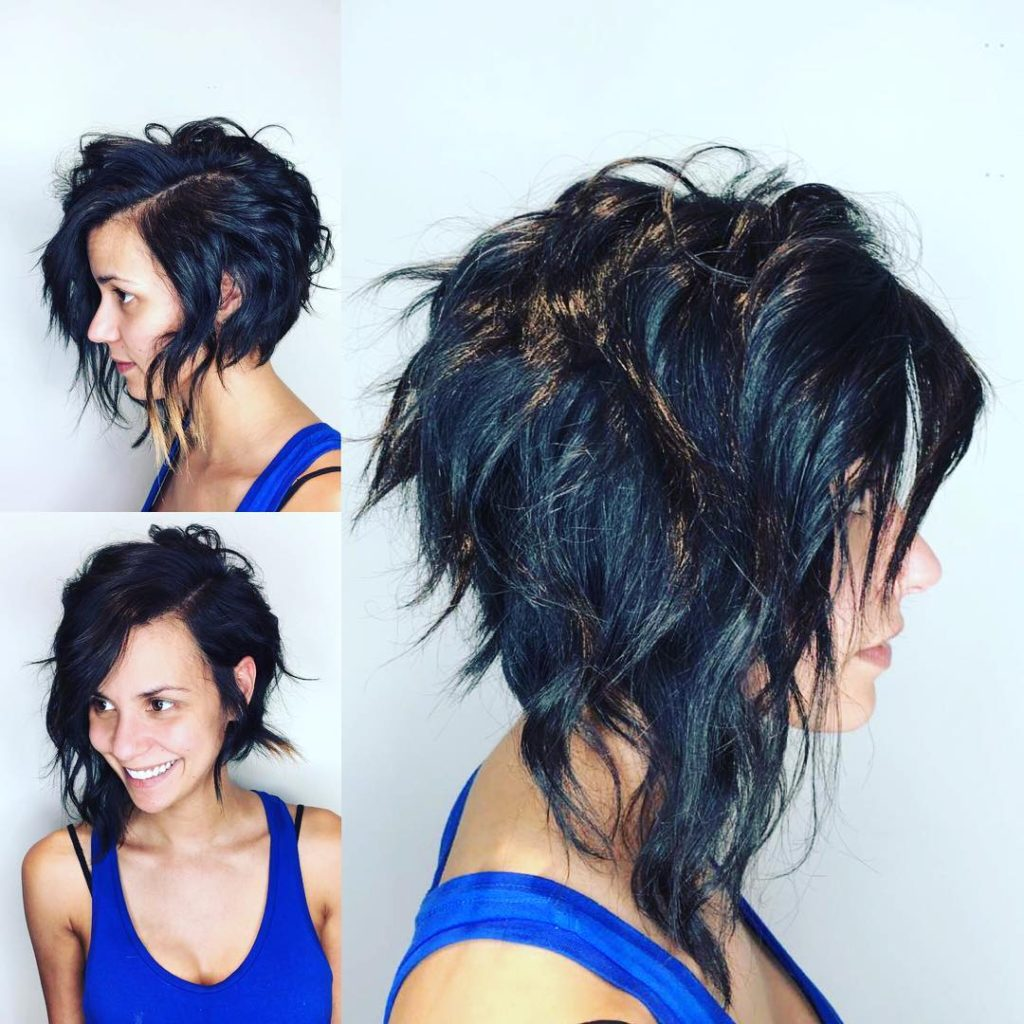 Edgy Angled Asymmetric Razor Cut Bob with Wavy Texture and Black Color Medium Length Hairstyle