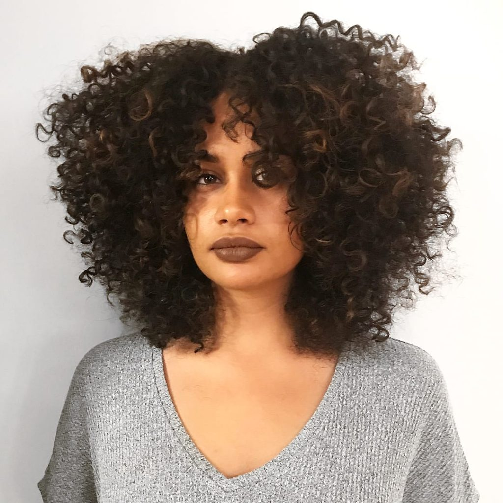 Highlighted Brunette Fro with Voluminous Spiral Curls and Disconnected Center Part Medium Length Hairstyle