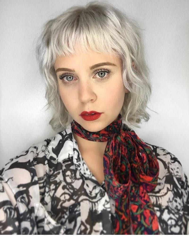 Icy Platinum Blonde Layered Bob with Messy Wavy Texture and Baby Fringe Medium Length Fall Hairstyle