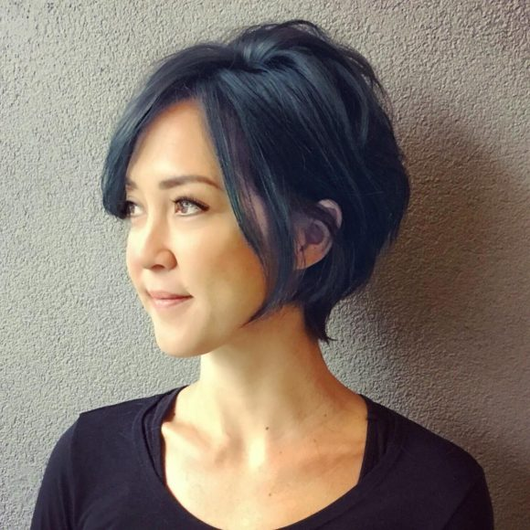 Inverted Razor Cut Bob on Smoky Blue Black Hair with Long Side Swept Bangs and Messy Texture Short Hairstyle