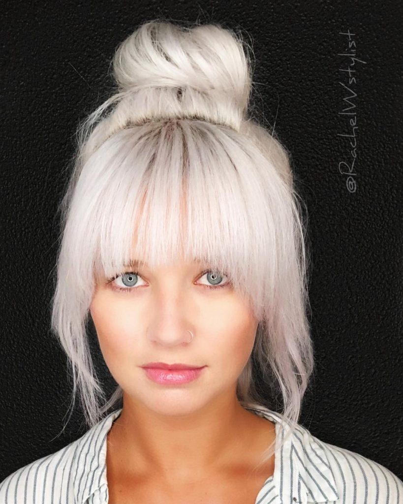Large Messy Top Bun with Full Face Framing Fringe and Platinum Blonde Hair Color Longhair Updo Fall Hairstyle