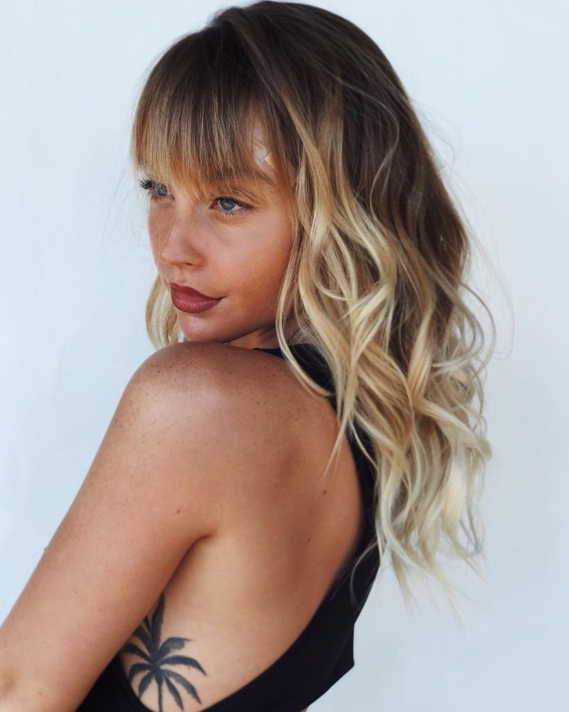 Layered and Banged Cut with Messy Boho Chic Waves and Sun Kissed Blonde Balayage Medium Length Summer Hairstyle