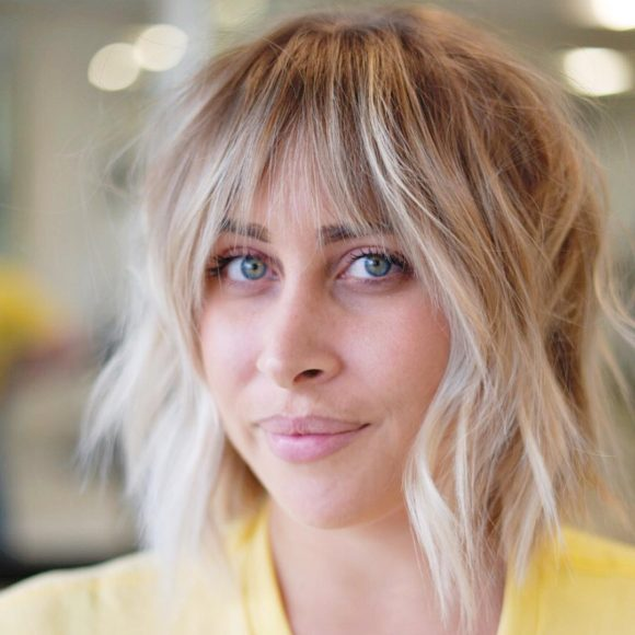 Light Blonde Choppy Bob with Messy Wavy Texture and Brow Skimming Bangs Medium Length Summer Hairstyle