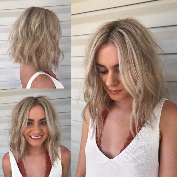 Long Light Blonde Angled Bob with Wavy Textured Layers and Babylights Medium Length Summer Hairstyle