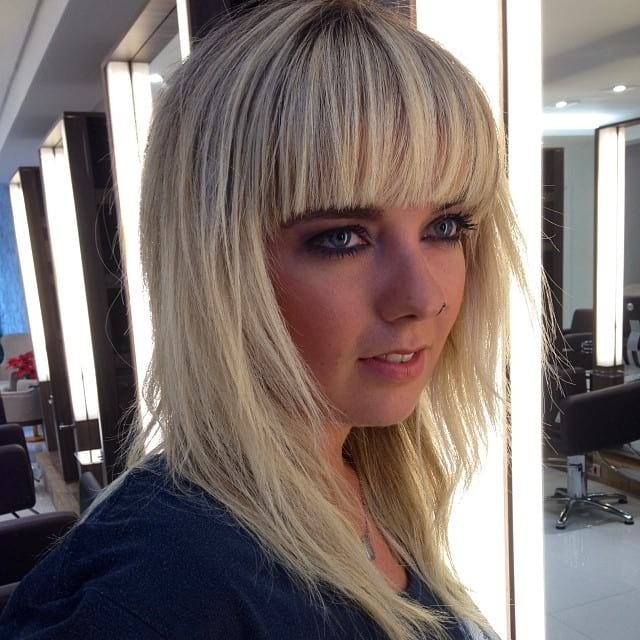 Long Shaggy Hair with V-Cut Layers and Full Blunt Bangs on Blonde Hair with Dark Roots
