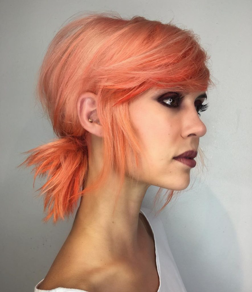 Low Messy Textured Ponytail with Side Swept Bangs and Pink Coral Hair Color Medium Length Updo Hairstyle