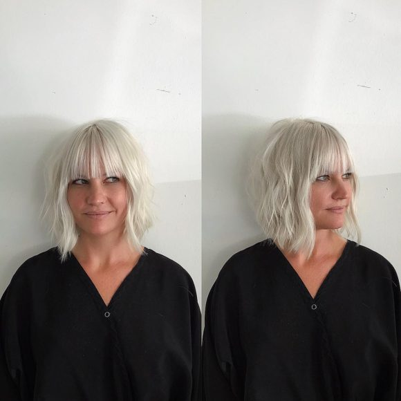 Modern Platinum Angled Bob with Wavy Texture and Bangs Medium Length Hairstyle
