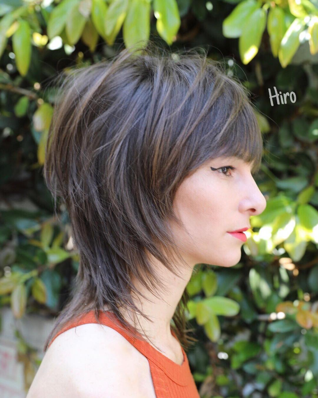 Shaggy Banged Mullet with Face Framing Fringe on Brunette Highlighted Hair with Messy Beach Texture Short Summer Hairstyle