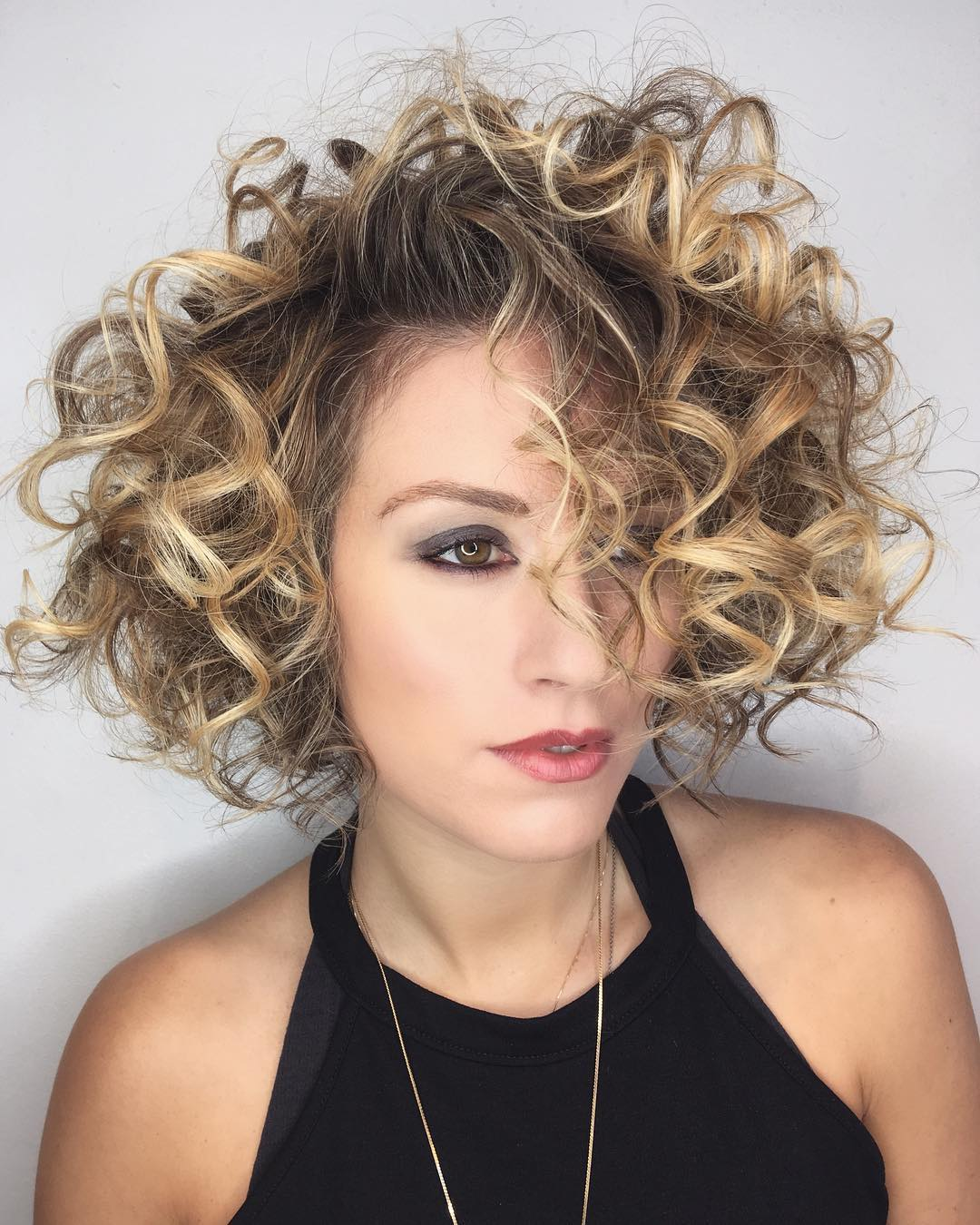 Shaped Bob with Large Messy Spiral Curls and Blonde Balayage Hair Color Medium Length Fall Hairstyle