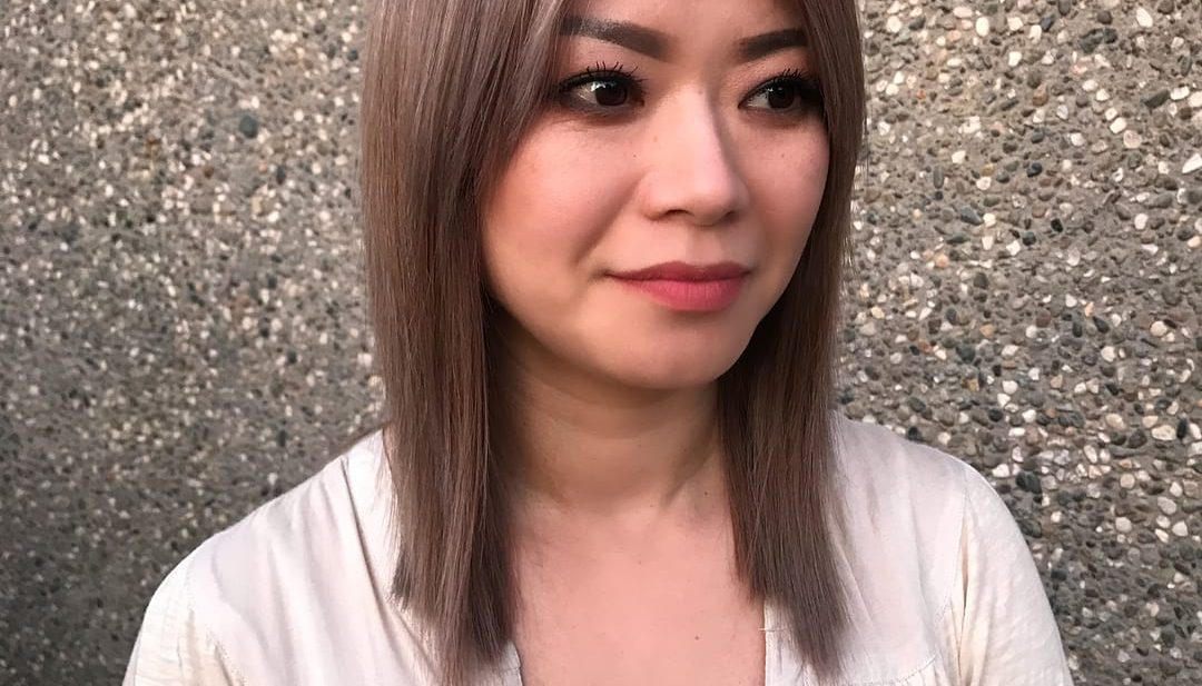 Straight Smoky Rose Gold Colored Lob with Blunt Lines and Curtain Bangs Medium Length Hairstyle