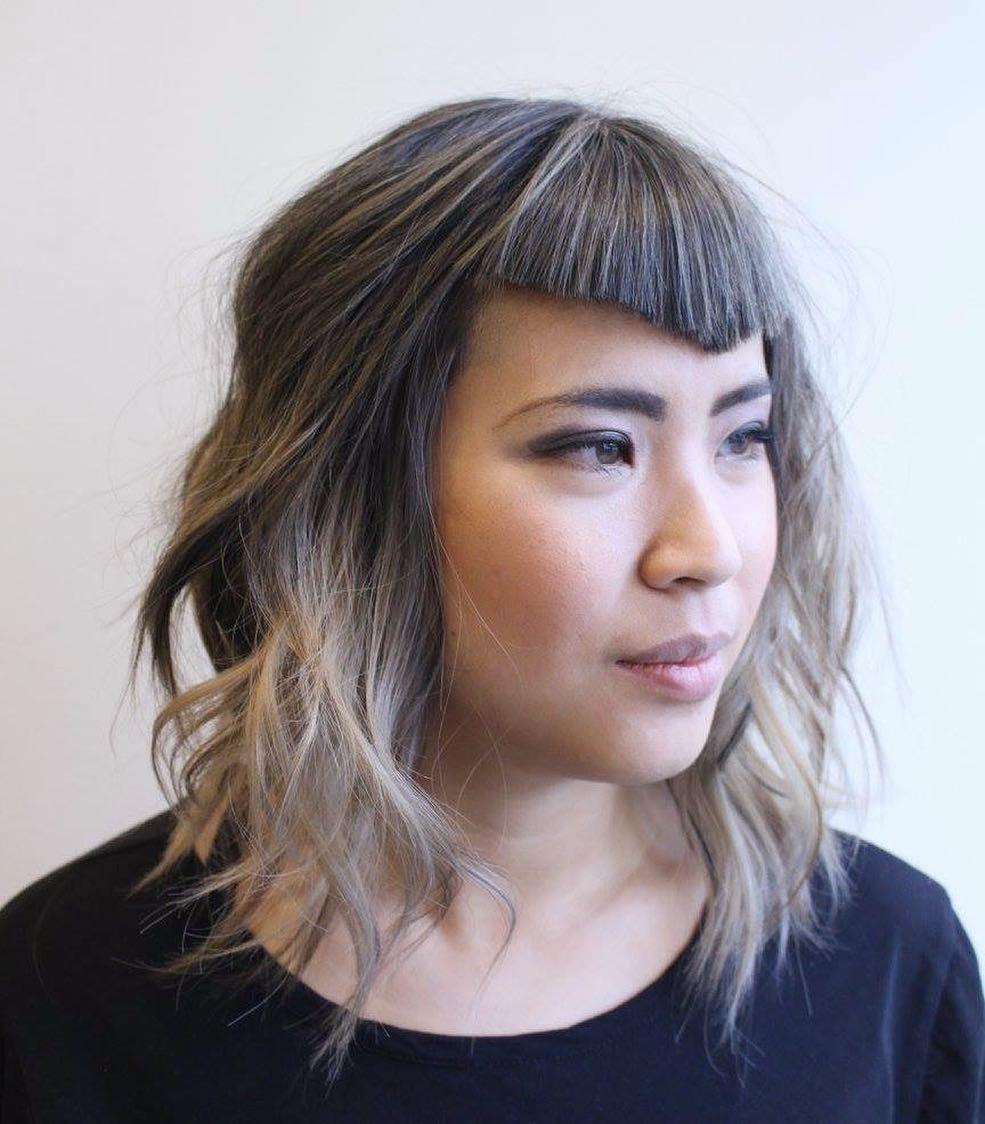 Undone Wavy Lob with Angled Fringe Bangs and Smoky Blonde Balayage Medium Length Hairstyle