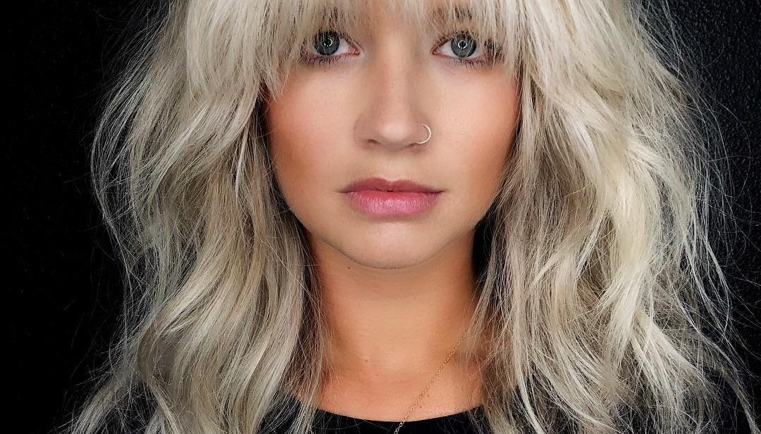 Voluminous Blonde Layered Lob with Face Framing Fringe and Messy Wavy Texture Medium Length Fall Hairstyle