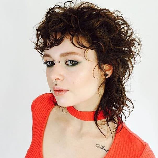 Warm Brunette Shaggy Mullet with Messy Curly Texture and Undone Fringe Medium Length Retro Fall Hairstyle