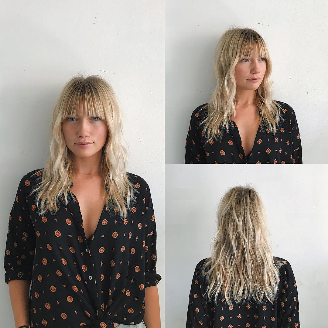 Wavy Blonde Layered Cut with Brow Skimming Bangs and Highlights Medium Length Hairstyle