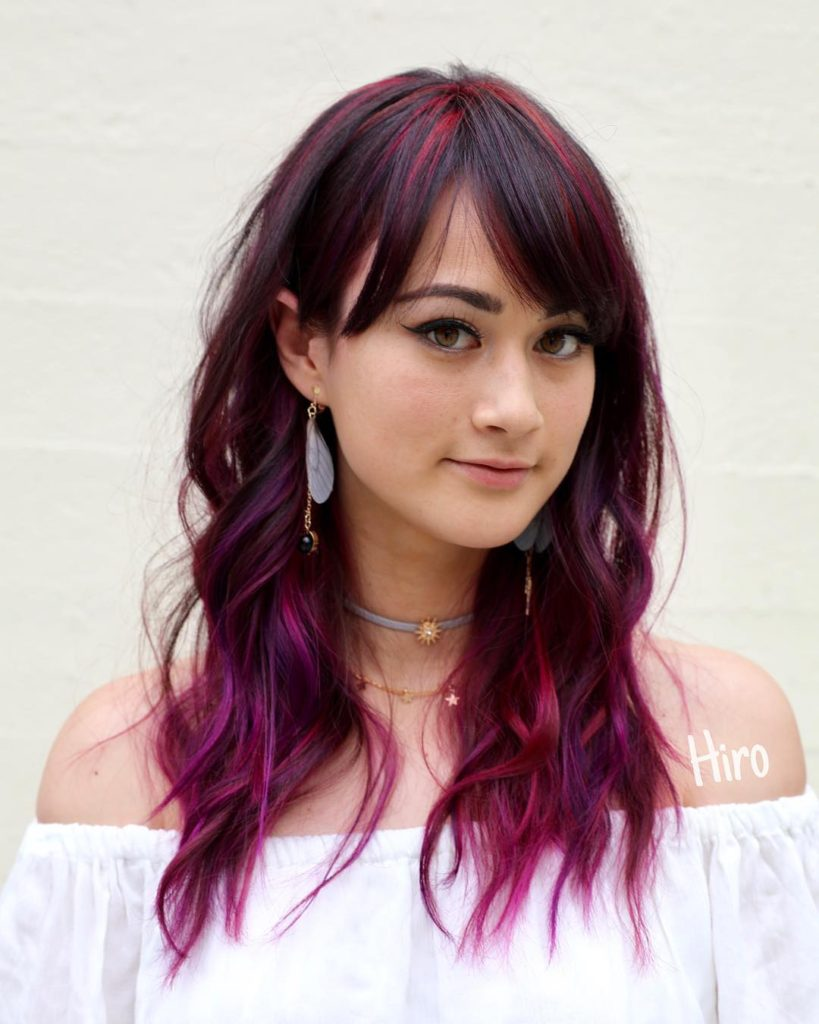 Wavy Mid-Length Layered Cut with Brow Skimming Bangs and Brunette to Magenta Hand Painted Hair Color Medium Length Summer Hairstyle