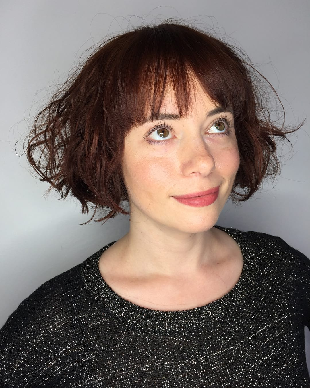 Wild Waves on a Short Dark Red Bob with Brow Skimming Bangs Short Hairstyle