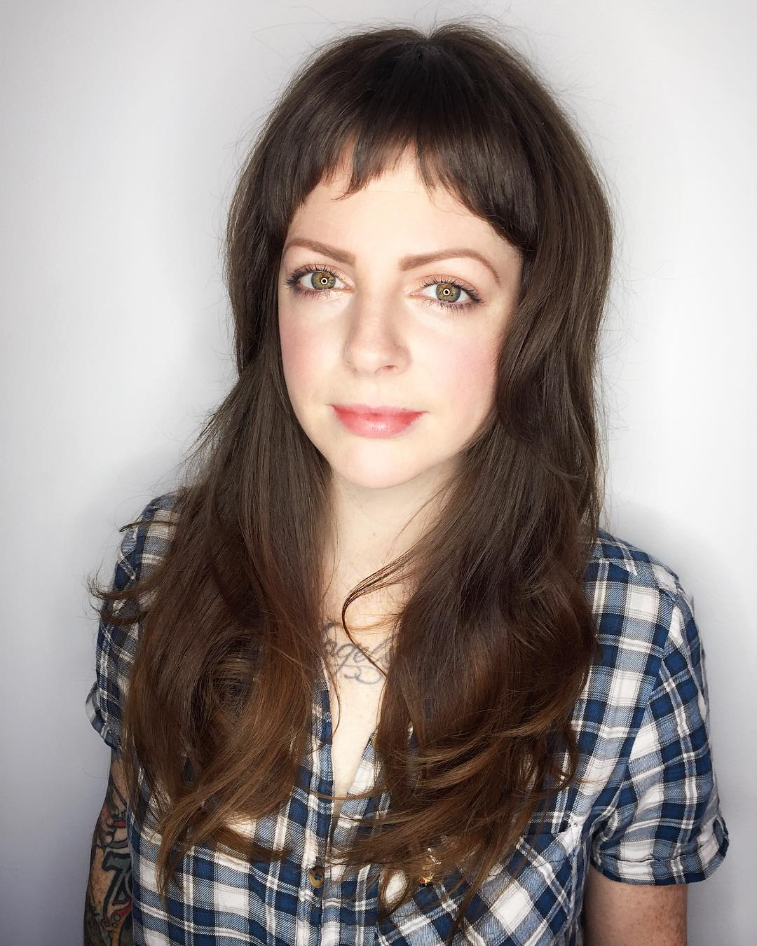 Long Wavy Layered Hair with Baby Fringe Bangs on Brunette Colored Hair with Lightened Ends