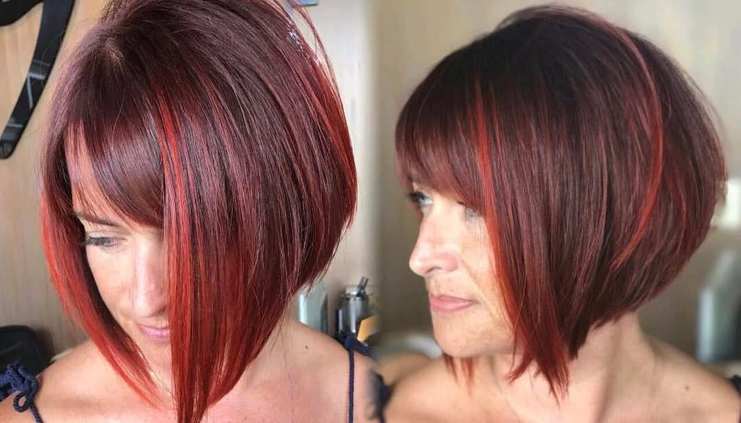 Inverted Bob with Side Swept Bangs on Burgundy Hair with Red Highlights
